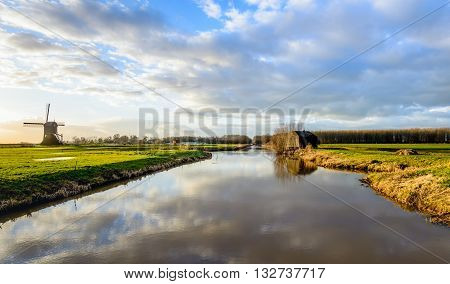 Picturesque view of a Dutch historical area with a bunker of the New Dutch Water Line and a mill from 1699 along a canal. It is the end of a sunny day in winter. Clouds are reflected in the water.