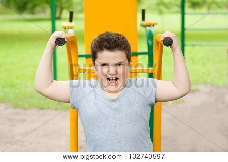fat boy trains on fitness equipment in the park