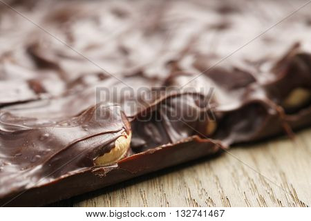 whole homemade bar of chocolate with cashew nuts reverse side, on wooden board shalow focus
