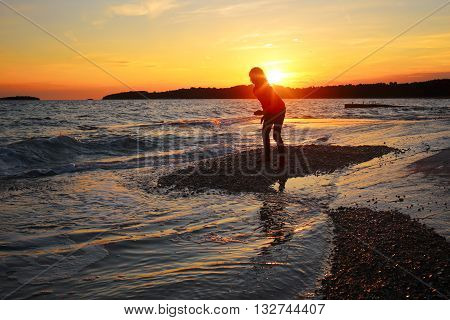 girl is playing on a beach at sundown