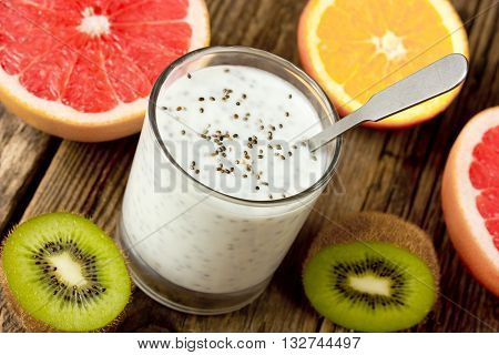 Healthy breakfast or morning snack with chia seeds yogurt pudding and fruit on wooden rustic background vegetarian food diet and health concept