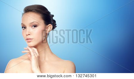 beauty, jewelry, accessories, people and luxury concept - face of beautiful young asian woman with golden ring over blue background