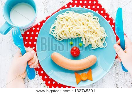 Dinner or breakfast for kids - clown face spaghetti with sausage and vegetables. Creative food art idea for children meal. Child eat his hands hold a fork and knife