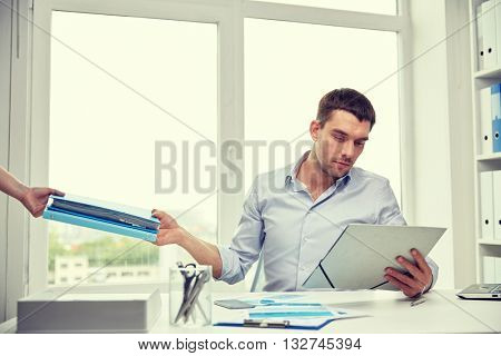 business, people and paperwork concept - businessman taking folder with papers from secretary in office