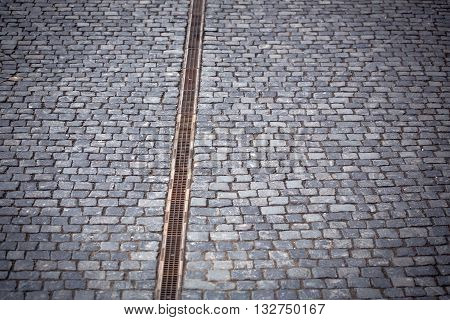 Paved road with drain water cover on grey cobblestone background
