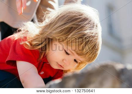 Cute little boy with long hair is interested in something