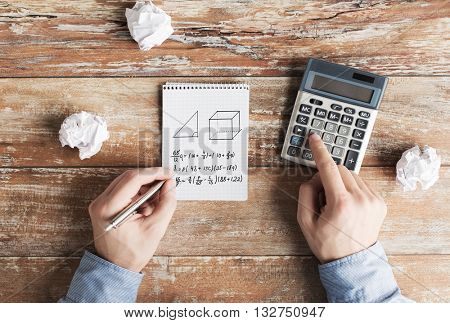 business, education, people and technology concept - close up of male hands with calculator, cramped paper wads and notebook solving geometric task