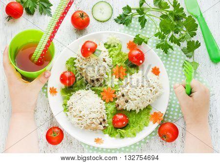 Food art idea for children dinner: steamed hedgehogs meatballs on vegetable garnish glade. Child eating concept top view
