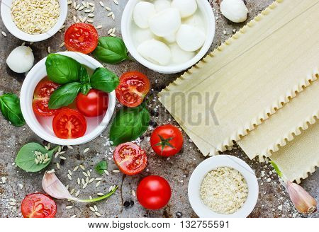 Italian food background concept products - cherry tomatoes basil mozzarella parmesan garlic spices pasta lasagna top view
