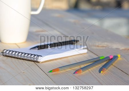 Items for Making Hand Notes Diary on Fresh Raw Light Wood Desk Opened Sketchbook Color Pencils and Black Pen White Coffee Mug