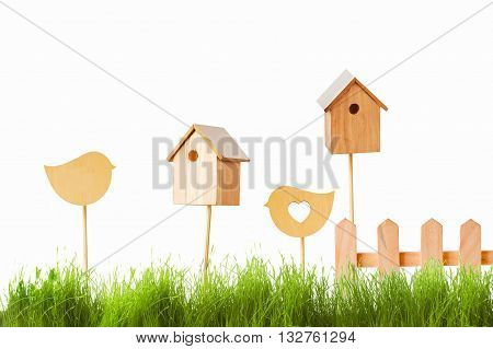 birdhouses and wooden bird on a background of green grass