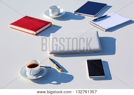 Coffee Mug Computer Pen Blue and Red Notepad Telephone Located on