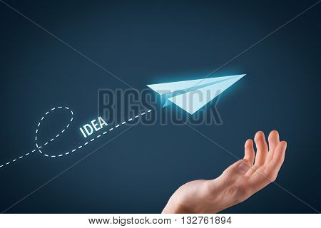 Idea and creative process concept. Paper plane representing dreaming about ideas and hand touching this dream comes true.
