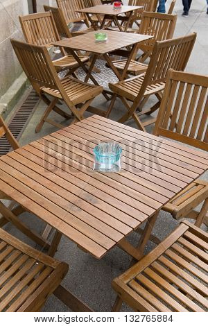 image of wooden tables of street cafe closeup