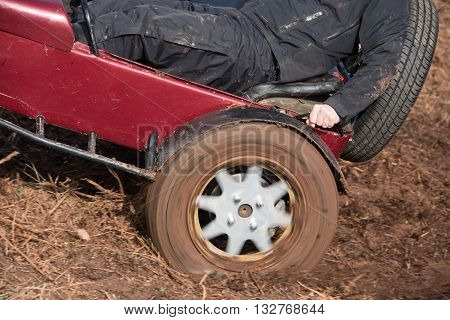 Close up view of the rear wheel of a car spinning trying to get up a muddy field