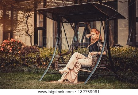 Beautiful Blond Red-haired girl model rests in swing boat garden house alcove