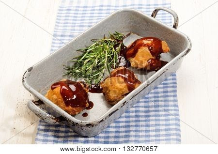 chicken thigh with barbecue sauce in rustic grey roasting pan