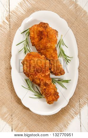 hot chicken drumstick with rosemary on oval plate
