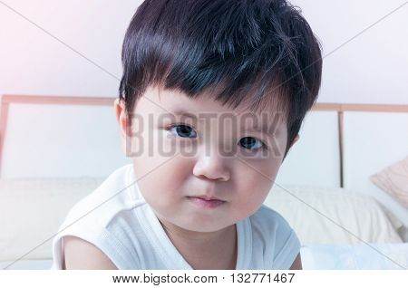 Asian boy toddler smiling white shirt shot at close range.