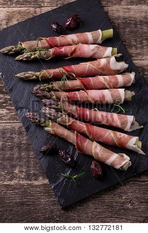 Fresh Organic Asparagus Wrapped In Parma Ham On A Cutting Board