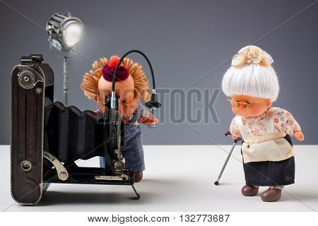 Puppets of senior photographer taking pictures of his old ladies with vintage camera in studio