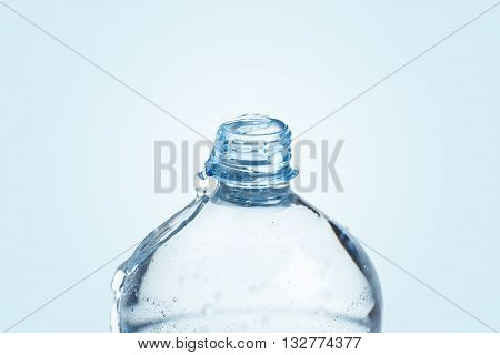 Overflowing with water plastic bottle on blue background