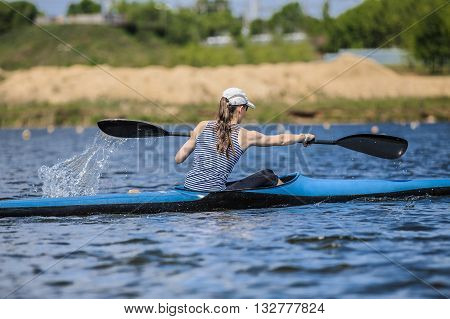girl at rowing kayak on lake during competition. spray of water under oars