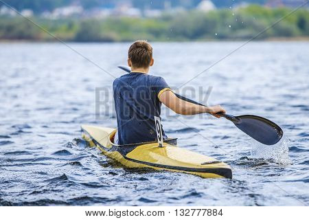 young man in a canoe rowing oars. boating in lake