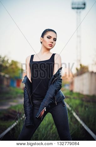 Outdoor fashion shot: a gorgeous young girl in black jacket shirt and jeans