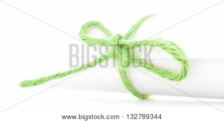 Handmade green string knot tied on white paper package isolated