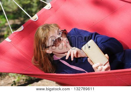 Woman Making A Quiet Gesture. Young woman in glasses on red hammock taking pictures with cell phone smartphone. Redhead woman with freckles. Forest mountains in background.