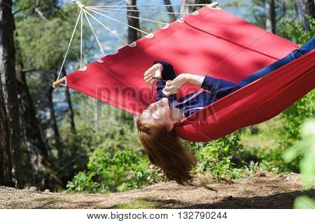 Happy Girl Relaxing In Hammock. Young woman wears glasses on red hammock in forest. Redhead woman with freckles smiles. Forest mountains in the background.