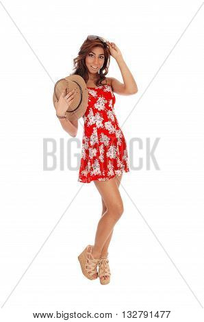 A pretty young woman in a red dress and curly brown hair holding a cowboy hat isolated for white background.