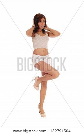 A tall gorgeous woman standing on one leg smiling in beige shorts isolated for white background.