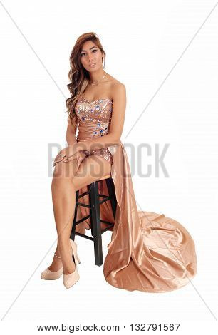 A lovely young woman in a gold color evening dress sitting on a chair with her legs showing isolated for white background.