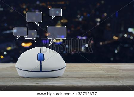 Wireless computer mouse with social chat sign and speech bubbles on wooden table in front of blurred light city tower Social network concept