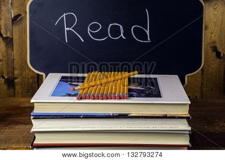 stack of books and pencils on wood background in front of chalkboard written read
