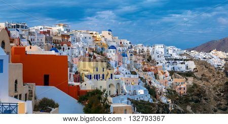 Panoramic view of white houses, windmills and church with blue domes in Oia or Ia, island Santorini, Greece