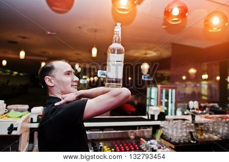 Barman Hold Bottle On Elbows Of Hand At The Bar