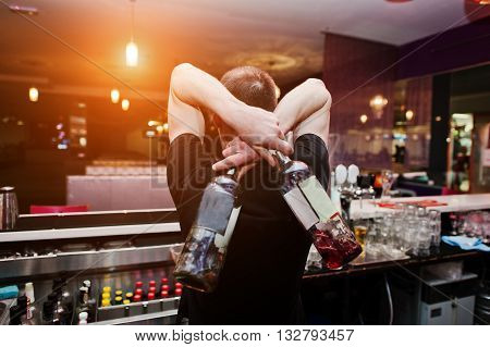 Young Barman Holding Bottles For Coctail At The Bar