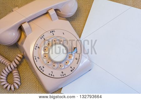 Vintage rotary telephone next to blank white paper