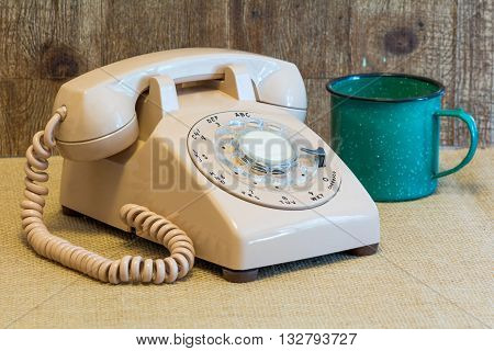 Vintage rotary phone next to an old style coffee cup