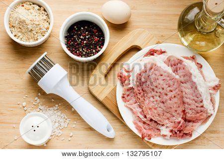 Recipe step by step: raw pork loin chops bread crumbs salt pepper oil egg on wooden table top view