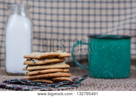 Chocolate chip cookies with a metal coffee cup and bottle of milk