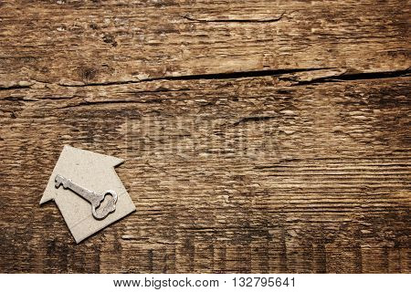 Cardboard house and key on wooden background. Construction of wooden buildings