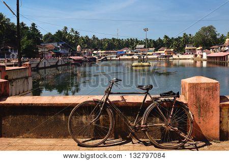 View to the sacred lake Kotiteerkha in Gorarna, Karnataka, India. Old bicycle is standing near lake railing