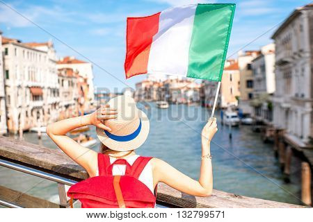 Young female traveler with italian flag on the bridge with geat view on Grand canal in Venice. Back view