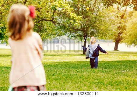 Kids play with a racquet and ball in the park