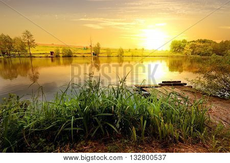 Beautiful yellow sunset over wooden pier on pond