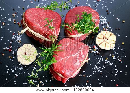 Fresh Raw Beef steak Mignon, with salt, peppercorns, thyme. Ready to cook